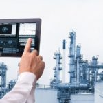 Man_hand_holding_cell_phone_or_tablet__automate_wireless__in_smart__oil_and_chemical_refinery__factory._Adobe_Stock