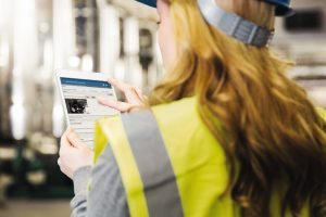 Woman_wearing_reflective_vest_controlling_industrial_plant_with_digital_tablet